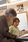 Oakland CA Volunteer tutor helping 1st grader with her reading in class