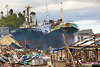 Philippines. Province Leyte. Tacloban. The Tomi Elegance and another ship have been pushed to the shore by typhoon Haiyan's winds and storm surge. Houses blown, washed away and destroyed. Men walk among houses's rubble and collects items for reconstruction. Typhoon Haiyan, known as Typhoon Yolanda in the Philippines, was an exceptionally powerful tropical cyclone that devastated the Philippines. Haiyan is also the strongest storm recorded at landfall in terms of wind speed. Typhoon Haiyan's casualties and destructions occured during a powerful storm surge, an offshore rise of water associated with a low pressure weather system. Storm surges are caused primarily by high winds pushing on the ocean's surface. The wind causes the water to pile up higher than the ordinary sea level. 1.12.13 © 2013 Didier Ruef