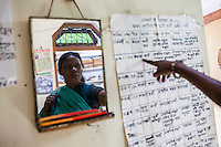 Shanti Adivasi (in green saree), 52, looks at a chart on the wall of the Khabar Lahariya district office in Manikpur, Chitrakoot, Uttar Pradesh, India on 5th December 2012. Shanti used to be a wood gatherer, working with her parents since she was 3, and later carrying up to 100 kg of wood walking 12km from the dry jungle hills to her home to repack the wood which sold for 3 rupees per kg. After learning to read and write in an 8 month welfare course, at age 32, she became a reporter, joining Khabar Lahariya newspaper since its establishment in 2002, and making about 9000 rupees per month, supporting her family of 14 as the sole breadwinner. Photo by Suzanne Lee for Marie Claire France.