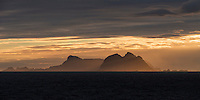 Værøy islands rise over sea while illuminated by winter sunset, Moskenesøy, Lofoten Islands, Norway
