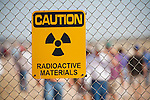 """Site Trinity, ground zero, on the White Sands Missile Range in S. New Mexico. Fence with radioactive sign and tourists during openhouse viisit. Site of the world's first atomic explosiion on August 6, 1945. The atomic bomb was developed by the Manhatten Project. The Manhattan Project refers to the effort during World War II by the United States, in collaboration with the United Kingdom, Canada, and other European physicists, to develop the first nuclear weapons. Formally designated as the Manhattan Engineering District (MED), it refers specifically to the period of the project from 1942-1946 under the control of the U.S. Army Corps of Engineers, under the administration of General Leslie R. Groves, with its scientific research directed by the American physicist J. Robert Oppenheimer. The project succeeded in developing and detonating three nuclear weapons in 1945: a test detonation on July 16 (the Trinity test) near Alamogordo, New Mexico; an enriched uranium bomb code-named """"Little Boy"""" detonated on August 6 over Hiroshima, Japan; and a plutonium bomb code-named """"Fat Man"""" on August 9 over Nagasaki, Japan. (http://en.wikipedia.org/wiki/Manhattan_Project)"""