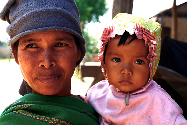 A Bahnar woman poses with her child for a photograph near the Central Highlands town of Kon Tum, Vietnam. The Bahnar are one of more than two dozen hill tribes known formerly in the West as Montagnards, but who are now called the Dega. April 14, 2012.