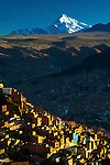 Snowcapped Mt Huayna Potosi rises above the crowded hillside homes in the city of La Paz.  The Altiplano highlands perch just above La paz, a city that flows from the hillsides into a canyon below.
