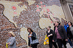 Shoppers walk beneath a world map on a bakery business hoarding.