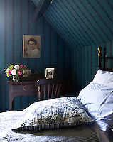 An iron bed, plumped up with pillows and quilted fabrics, combined with a bold wallpaper makes for a cosy bedroom