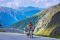 Female cyclist on the Umbrail Pass which leads, in the Swiss National Park, from Switzerland to Italy in the Eastern Alps