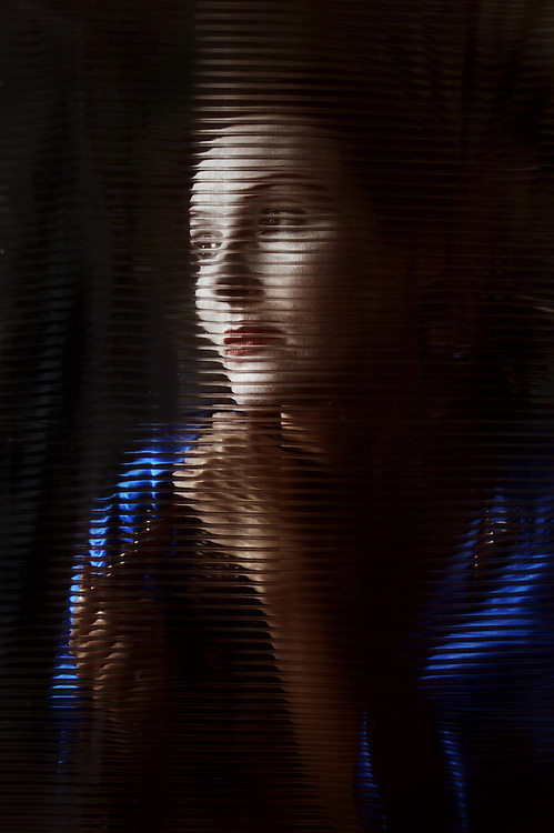 asian dressed woman sitting behind corrugated glass