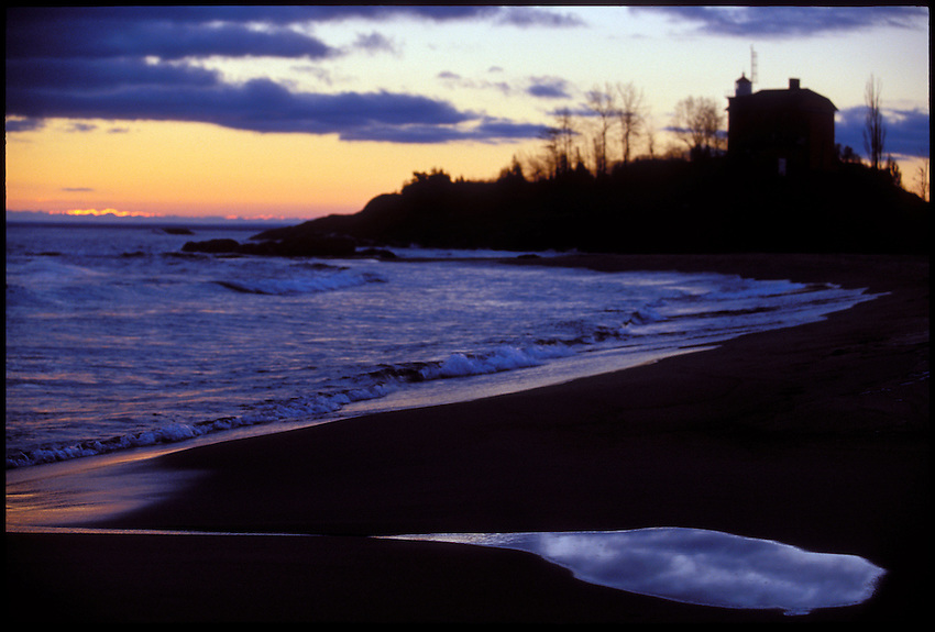 THE MARQUETTE LIGHTHOUSE IS SILHOUETTED AT DAWN AS CLOUDS REFLECT IN A PUDDLE ON A LAKE SUPERIOR BEACH IN MARQUETTE MICHIGAN.