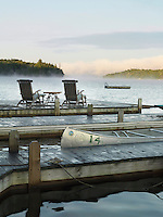 A pair of Adirondack chairs on one of the wooden jettys overlooking the lake in the calm of early morning