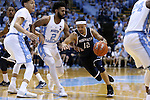 28 December 2016: Monmouth's Justin Robinson (12) drives past North Carolina's Joel Berry II (2) and Justin Jackson (left). The University of North Carolina Tar Heels hosted the Monmouth University Hawks at the Dean E. Smith Center in Chapel Hill, North Carolina in a 2016-17 NCAA Division I Men's Basketball game. UNC won the game 102-74.