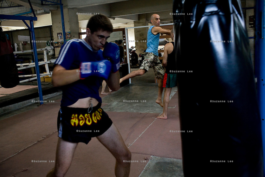 "Shuki (second from right) demonstrates the techniques for a 'flying elbow' to Eran (right) while Ilya (left) train with punching bags in Rompo Muay Thai Gym, Khlong Toei, Bangkok city, Thailand on 14th December 2009..Shuki Rosenzweig, aged 40, is a professional Muay Thai Boxing fighter (champion) and trainer who has lived for 9 years in Thailand. He is famous in Israel as the authority of this sport. Started at the age of 12 in boxing in Israel, Jerusalem. Used to work in the fish market. His father is a 'legend' in Jerusalem fish market. Shuki stopped working with his dad about 13 years ago. He has opened some muay thai gyms in Thailand in the past. He currently has about 5 Israeli fighters under his training in Bangkok, besides fighters of other nationalities. Shuki found religion in Bangkok with Chabad about 4 years ago. He never misses Shabbat and loves to sing the songs of prayer, priding himself with a good voice. ""Chabad integrates all Jews. it keeps us together. When at Chabad, we are at home, united with people of the same culture, language and beliefs""..Eran Schwartz, aged 30, from Jerusalem, has been training for 8 years. He trains for endurance, fitness and fun, although he has fought in one competition in Bangkok the last time he was here. ""Eran is very talented, technically adept, wise and has a 'good eye' for fights"" says Shuki. This time Eran is staying 3 and a half months in Thailand to train, travel, and write scripts for a TV show and a cartoon series. He had studied economics and used to work in a bank in Israel before he came here. Eran's grandparents are religious but he grew up being secular. ""Chabad never pushes you to be religious. It is a relaxed place, they accept you for what you are"" says Eran. ""It is important to go for Shabbat for all Jews on travel."".Ilya Bashes, aged 27, from Herzeliya, Israel, has been fighting seriously for 5 years. He met Shuki in a muay thai seminar in Israel and decided immediately that he would come to Thailand"