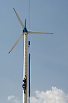 A worker climbs the mast of a 10KW wind turbine on the King's Wind Farm in Thailand. The farm is owned and operated by Prapai Technologies.