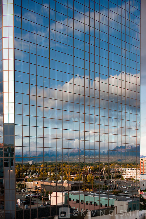 Photo of clouds and downtown Anchorage reflected in the glass windows of the Atwood Tower, wide angle lens looking up, Southcentral Alaska, USA.