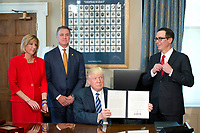 United States President Donald J. Trump holds up the order after signing the last of three Executive Orders concerning financial services at the Department of the Treasury in Washington, DC on April 21, 2017.  From left to right: US Representative Claudia Tenney (Republican of New York) US Senator David Perdue (Republican of Georgia), the President, and US Secretary of the Treasury Steven Mnuchin.<br /> Credit: Ron Sachs / Pool via CNP /MediaPunch
