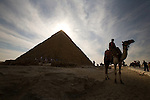 A camel and tourists at the Pyramids of Giza near Cairo, Egypt.