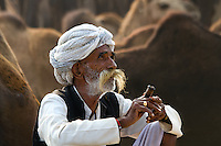 A Man with his Pipe. An eldery men smoking a chillum using hookah. Pushkar Camel Fair, Rajasthan, India.