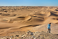 Hiker watching sand dunes, Saddle Hill, Sperrgebiet National Park, Namibia, Model release