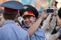 Moscow, Russia, 23//06/2011..A policeman sings along to the music as he uses a mobile phone to film American band Linkin Park perform by Red Square to mark the world premiere in Moscow of the new Michael Bay movie Transformers: Dark Of The Moon.