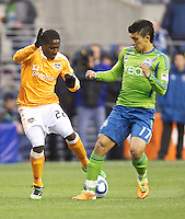 Houston Dynamo midfielder Lovel Palmer battles Seattle Sounders FC forward Fredy Montero for the ball  during play at Qwest Field in Seattle Friday March 25, 2011. The match ended in a 1-1 draw.