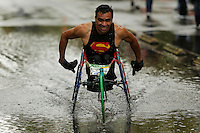 An athlete in category wheelchair, through a puddle of water while racing in the rain, during the 32nd Mexico City International Marathon held in Mexico City, capital of Mexico, on Aug. 31, 2014. The Mexico City Marathon is a Boston Marathon qualifier. Photo by Miguel Angel Pantaleon/VIEWpress