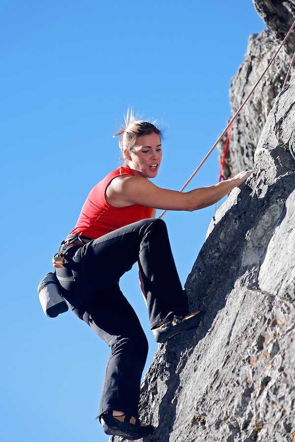 Female climber on rock face against blue sky, Banff, Banff National Park, Alberta, Canada