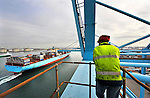 "A crane operator watches as the ""Elly Maersk"" departs from the APM Terminal at the Port of Rotterdam, on Tuesday Oct. 27, 2009, in Rotterdam, the Netherlands. The ""Elly Maersk"" one of eight PS-class container ships in the Maersk Line fleet,  and is one of the largest container vessels in the world. With an overall length of 397 meters and a width of 56 meters, it is capable of carrying 11,000 TEU (Twenty foot Equivalent Unit - a 20 foot long container). (Photo © Jock Fistick)"