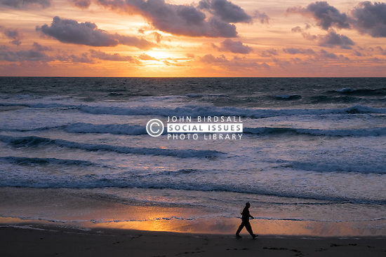 A man seen in silhouette as he walks across Fistral Beach at Sunset. Newquay, Cornwall.