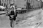 Belfast Northern Ireland, young Loyalist boy carries his sister through rainy depressing back streets on his shoulders, she is holding a Union Jack flag. The British army patrol this area of the inner city. 1970