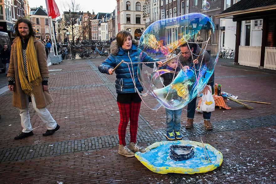 Nederland, Utrecht, 21 feb 2014<br /> Man laat kinderen op straat grote bellen blazen. Hij probeert daarmee ook zijn bellenblaasspullen te verkopen.<br /> <br /> Foto(c): Michiel Wijnbergh