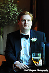 Groom reflects with a beer in soft window light prior to his ceremony..