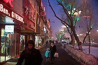 People walk along the streets of a shopping district in Urumqi, Xinjiang, China.