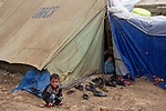 DOMIZ, IRAQ: A young Syrian refugee plays outside his tent in the Domiz refugee camp in the Kurdish region of northern Iraq...The semi-autonomous region of Iraqi Kurdistan has accepted around 60,000 refugees from war-torn Syria. Around 20,000 refugees live in the Domiz camp which sits 60 km from the Iraq-Syria border...Photo by Younes Mohammad/Metrography