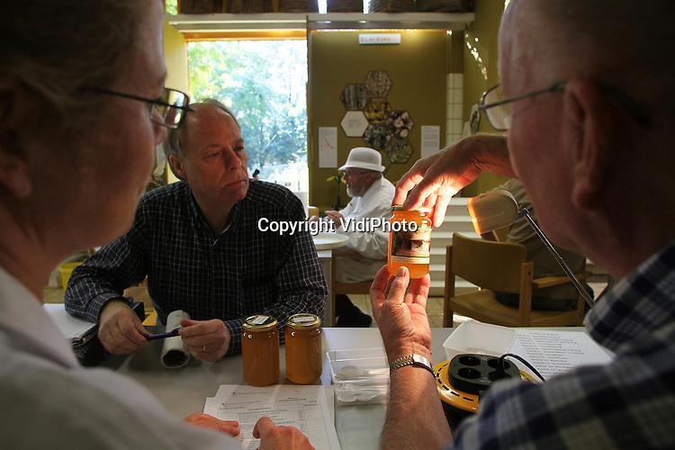 Foto: VidiPhoto..WAGENINGEN - In het zogenoemde Bijenhuis in Wageningen is zaterdag -voor het eerst in vele jaren- de nationale honingkeuring gehouden, georganiseerd door de drie Nederlandsen bijenbonden. Enkele tientallen potten met allerlei soorten honing van Nederlandse imkers werden door de keurmeesters aan de kwaliteits- en hygiënecontrole onderworpen. Nederland telt een kleine 30.000 bijenvolken van zo'n 5500 bijenhouders. Een bijenvolk levert tussen de 15 en 20 kilo honing per jaar. Nederland behoort tot de top in Europa als het gaat om de kwaliteit van de honing.