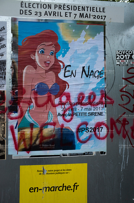 "France. Ile de France. Paris. Political opponents have glued a Little Mermaid poster on an official campaign poster  of French presidential election candidate Emmanuel Macron for the centrist party ""En Marche"". A graffiti with handwritten words says "" Refugees welcome"". The Little Mermaid is a 1989 American animated musical fantasy film produced by Walt Disney Feature Animation and released by Walt Disney Pictures. 22.04.17 © 2017 Didier Ruef"