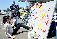 Elisa Gemme  adds her foot prints onto Animal Kingdom?s multi-species community art project during  the Pico de Mayo festival at the Santa Monica Civic parking lot on Sunday, May 27, 2012.