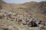 Members of the 82nd Airborne and Afghan villagers carry a cache of weapons, marijuana, and opium discovered in a remote mountain region of Kandahar province, Afghanistan on Monday, March 26, 2007.