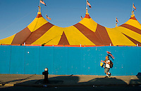 People walk to and from the beach by the circus at Coney Island. Street photography Brooklyn,  NY August 4, 2007