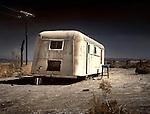 An old white caravan left to rot in the desert