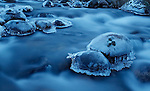 Ice coating stones in slow-moving stream in cold evening light, Cairngorms, Scotland