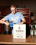 June 18, 2013. Chapel Hill, North Carolina<br />  Corey Bobeck, an employee of Top of the Hill Brewery, boxes bottles of TOPO Gin for shipping.<br />  TOPO, Top of the Hill Distillery, the brainchild of owner Scott Maitland and Spirit Guide Esteban McMahan, is located in the old N&amp;O Building on Franklin Street. Making gin, vodka and American whiskey from locally sourced wheat, they are one of the few distilleries bringing  organic liquor to ABC shelves around the state.