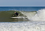 A surfer glides across a breaking wave at Whitecrest Beach in Wellfleet.