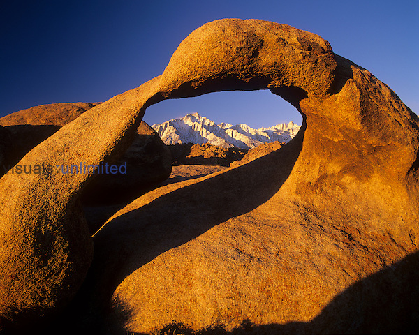 A natural arch in the Alabama Hills frames Lone Pine Peak 9left,and Mt. Whitney ,right, Eastern Sierra Nevada Mountains, California, USA.
