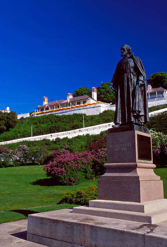 A STATUE OF FATHER JACQUES MARQUETTE STANDS AMON BLOOMING LILACS ON THE LAWN BELOW FORT MACKINAC ON MACKINAC ISLAND, MICHIGAN.