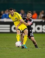 Chris Korb (22) of D.C. United fights for the ball with Justin Meram (9) of the Columbus Crew during the game at RFK Stadium in Washington, DC.  D.C. United defeated the Columbus Crew, 3-2.