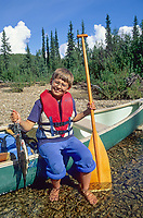 Boy holds catch of Arctic grayling on the shores of the Chatanika River, interior, Alaska