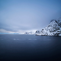 Snow covered mountains rise from sea, Å, Moskenesøy, Lofoten Islands, Norway