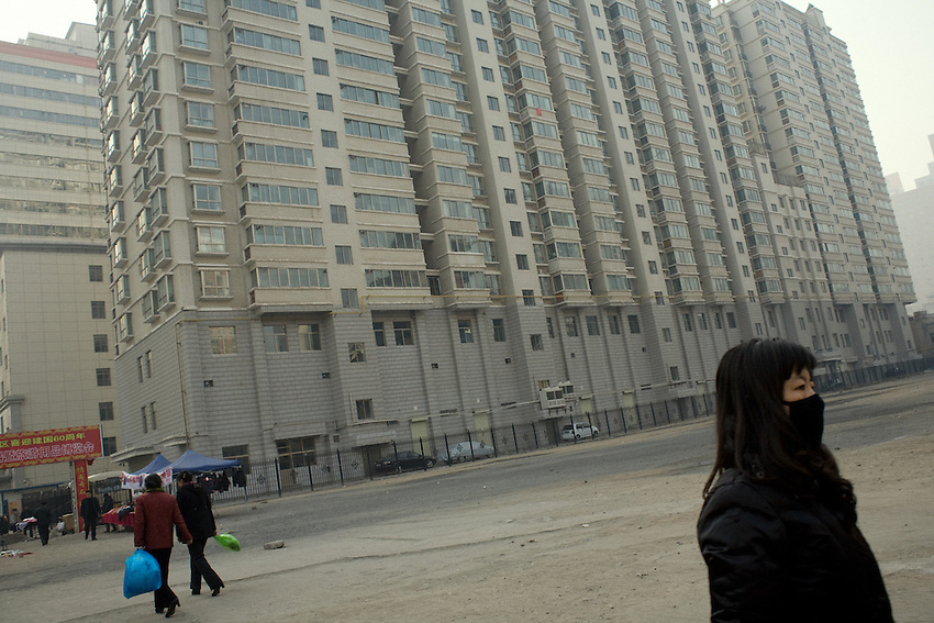 A  young chinese woman with a mask against pollution, near a high rise complex recently build in the center of Lanzhou.<br /> The whole town of is overlaid by a visible lay of pollution from automobile traffic and factories activity using coal. <br /> -------<br /> Lanzhou, in the Gansu province is the most polluted cities of China and in the world's top ten for atmospheric pollution due to human activity. The town is situated between two hills along the Yellow River and the polluted clouds remain blocked over the town. The sky is most of the time hidden by the pollution.
