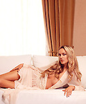Beautiful young glamorous woman with long golden hair lying on white sofa by the window