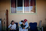 Lilia Parra cradles her nephew at her home in the Rancho Garcia trailer park in Thermal, Calif., March 9, 2012.