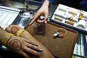 A newly married woman tries on gold bangles at a Mehrasons Jewellers store in New Delhi, India. Photo: Sanjit Das/Panos Pictures